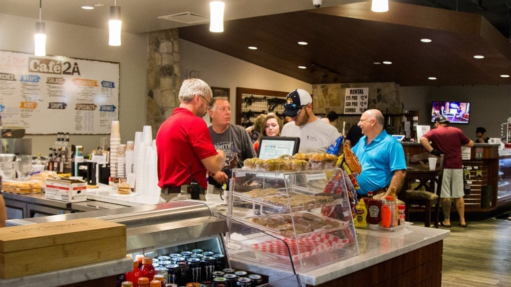 Customers ordering a coffee at the cafe before going to the range