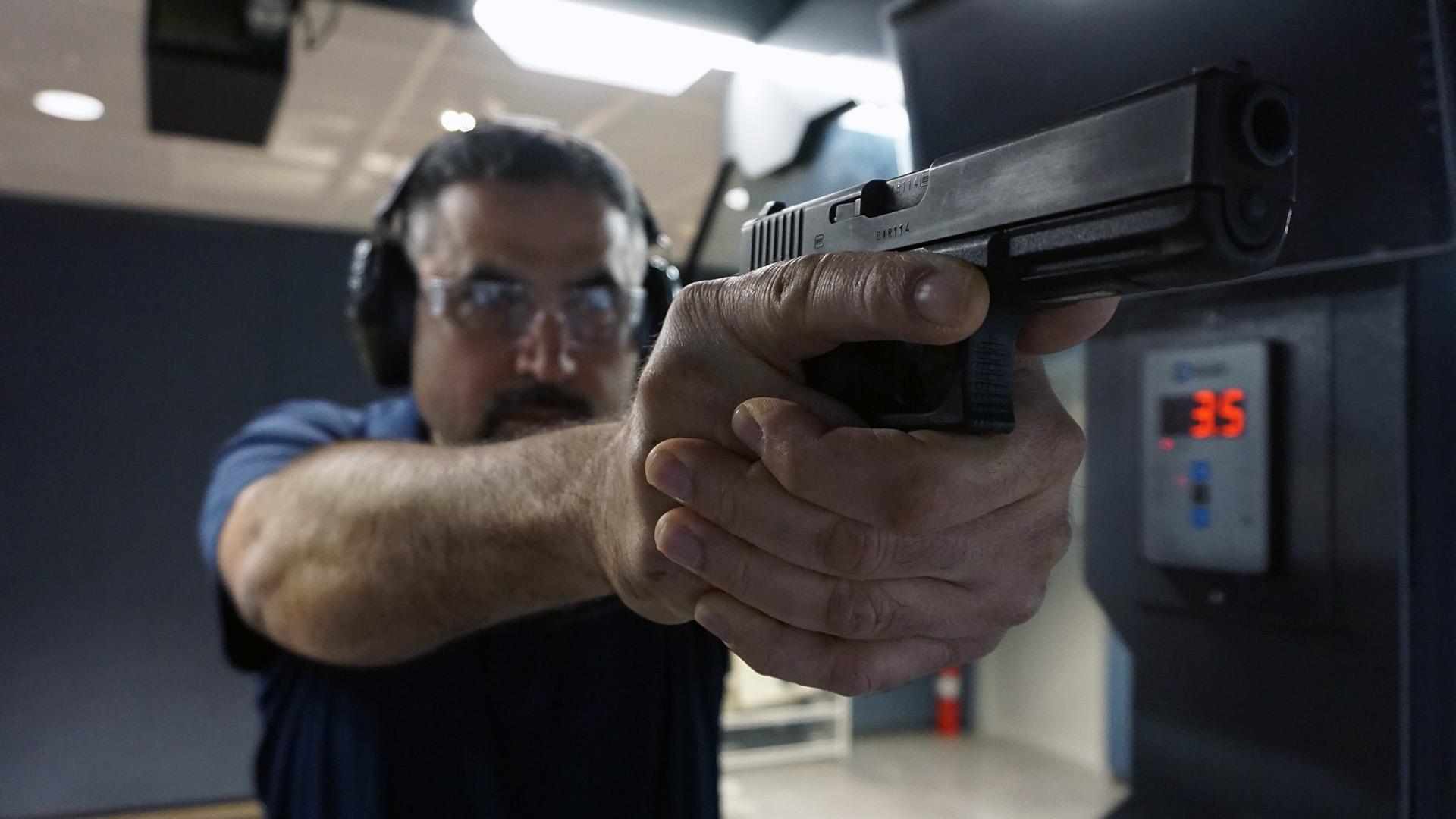 Image of man with handgun on range